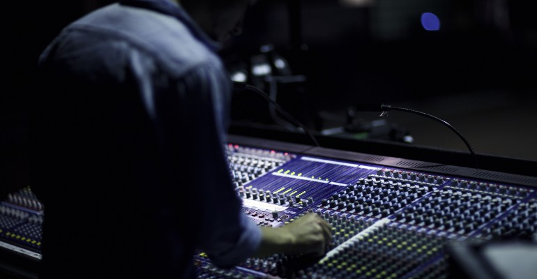 Sound engineer mixing the audio behind the audio console. Denmark 2011.